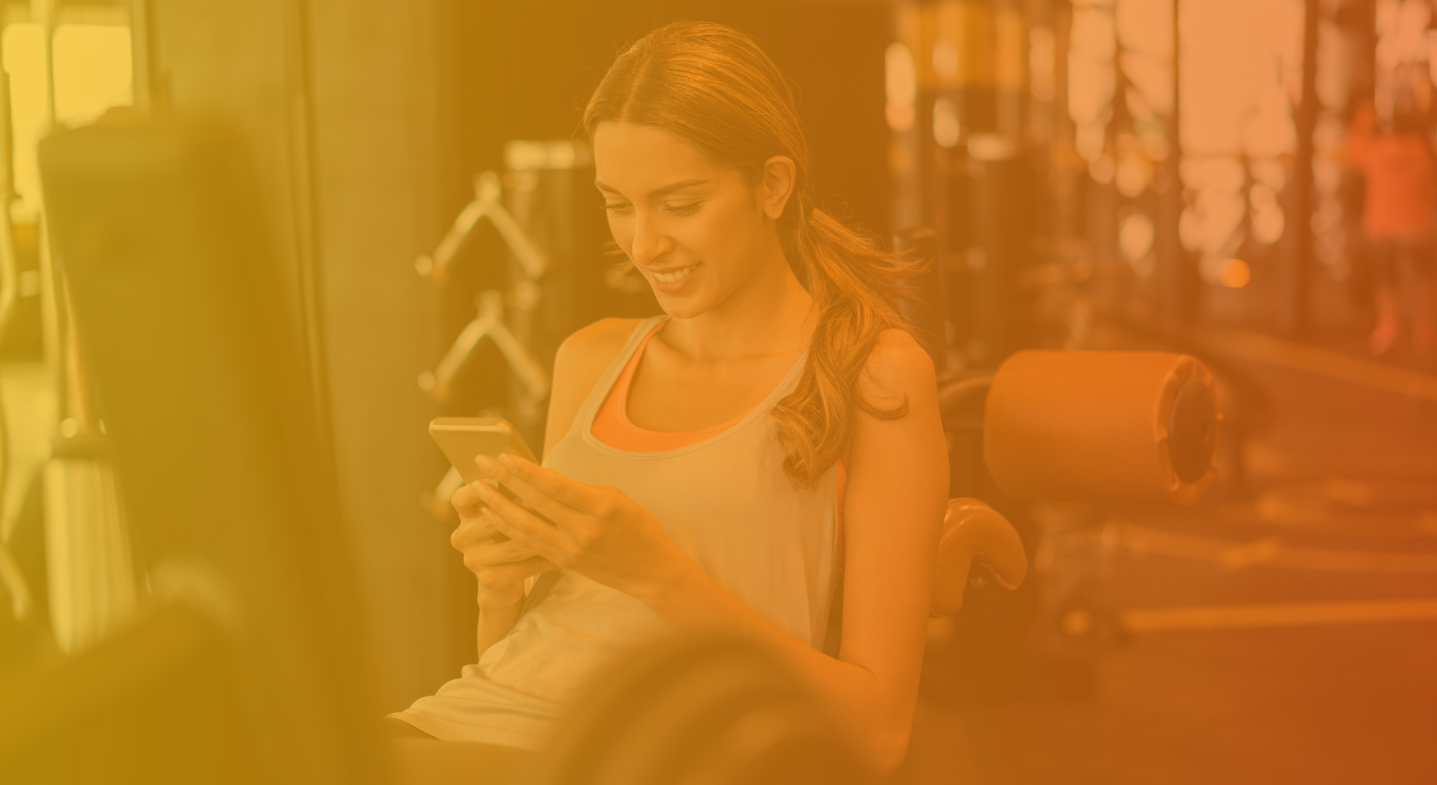 woman smiling at her phone in the gym
